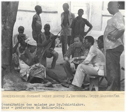 Image in black and white of people in consultation in Madina Oula