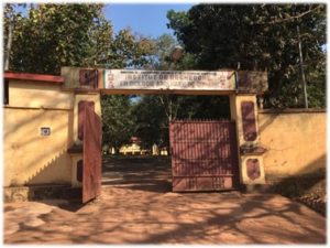 Photo of a half-open wooden gate with trees in the background
