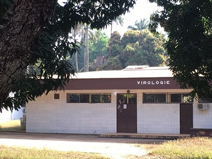 Photo of a building with the word virologie on it situated among trees